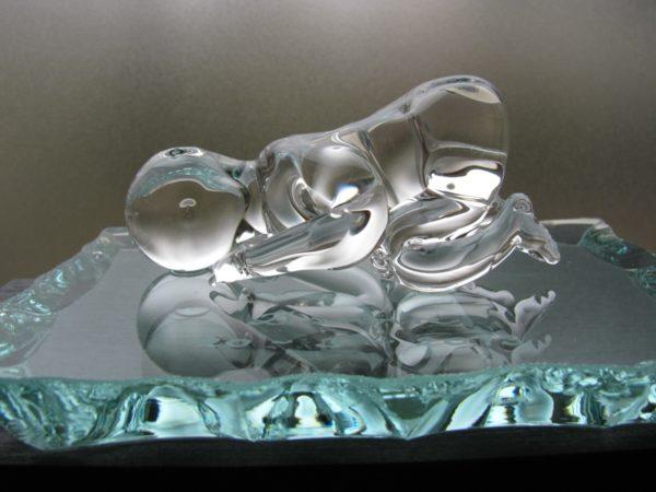 Glazen liggende baby op voetstuk